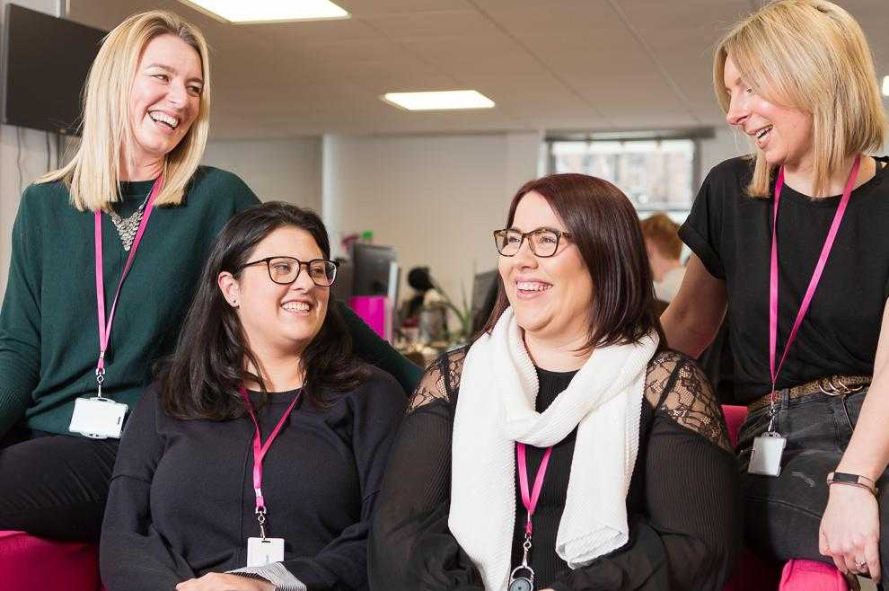 Four members of the Care Sourcer team smiling and laughing in the office